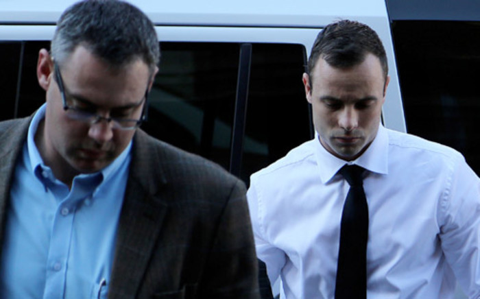 Oscar Pistorius is escorted into the High Court in Pretoria ahead of day 21 of his murder trial on 11 April 2014. Picture: Sebabatso Mosamo/EWN.