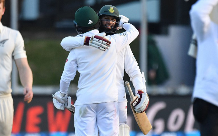 South Africa's Hashim Amla with teammate Jean-Paul Duminy celebrate after winning the 2nd test during day three of the second Test cricket match between New Zealand and South Africa at the Basin Reserve in Wellington on 18 March, 2017. Picture: AFP.