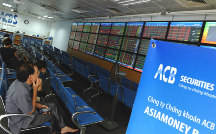 Investors sit watching share prices at an Asia Commercial Bank (ACB)'s securities trading floor in Hanoi on August 22, 2012. Picture: AFP.