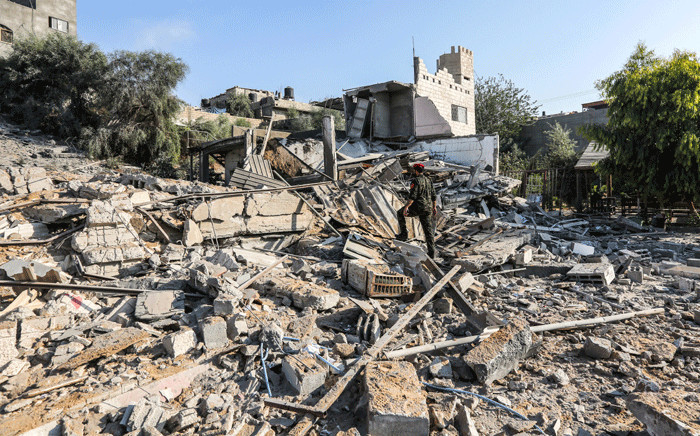 FILE: A member of Hamas' military police walks through rubble at a site that was hit by Israeli air strikes in Gaza City on 9 August 2018. Picture: AFP