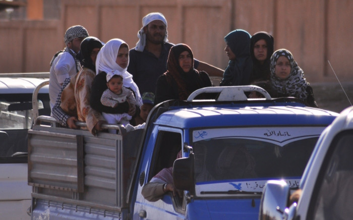 Displaced Syrians, who fled their homes in the northeast city of Hasakeh due to attacks by the Islamic State (IS) group, sit in the back of a pick-up truck driving in the Kurdish city of Qamishli, on the border with Turkey, on 26 June 2015. Picture: AFP.