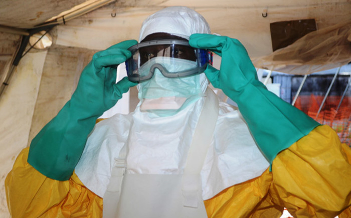 A member of Doctors Without Borders (MSF) putting on protective gear at the isolation ward of the Donka Hospital in Conakry, where people infected with the Ebola virus are being treated. Picture: AFP.