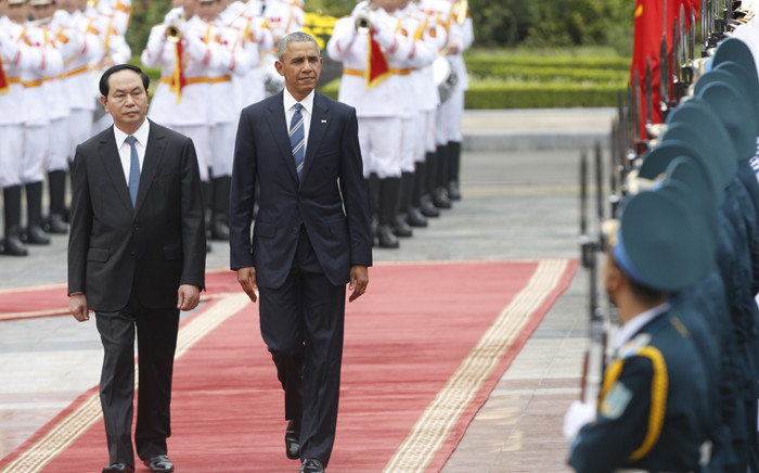 US President Barack Obama (C) walks with his Vietnamese counterpart Tran Dai Quang (L) as they review a guard of honour during a welcoming ceremony at the Presidential Palace in Hanoi on 23 May, 2016. Picture: AFP.