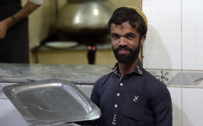 In this picture taken on 22 February 2019, Rozi Khan, a 25-year-old Pakistani waiter who resembles US actor Peter Dinklage, looks on at Dilbar Hotel in Rawalpindi. Picture: AFP