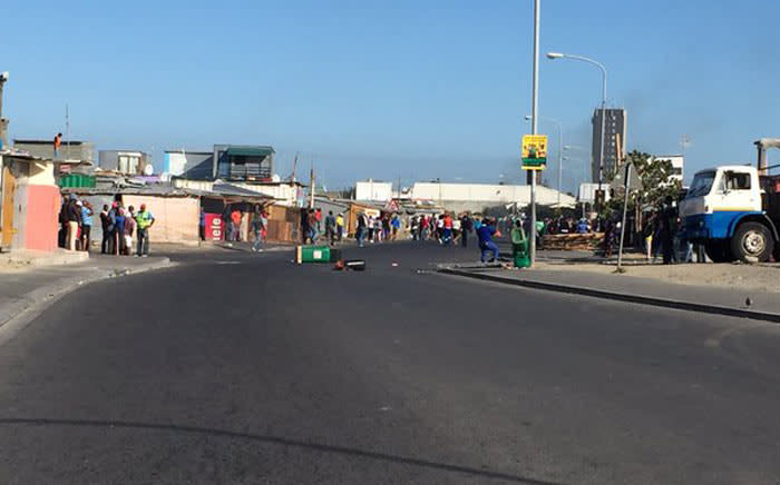 The crowd quickly disperses between shacks as protesters respond to approaching police in Montague Gardens by throwing stones. Picture: Natalie Malgas/EWN.