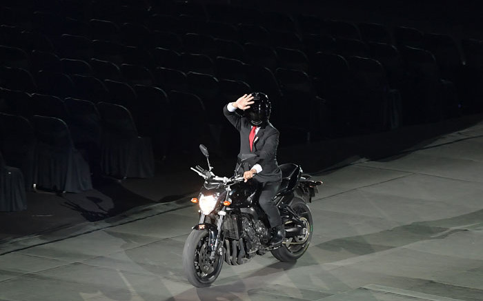 An actor impersonating Indonesian President Joko Widodo waves while riding a motorbike during the opening ceremony of the 2018 Asian Games at the Gelora Bung Karno main stadium in Jakarta on 18 August, 2018. Picture: AFP