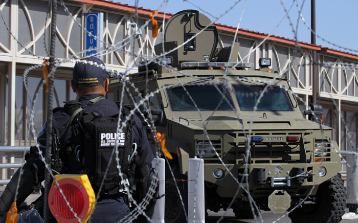 FILE: A US Customs and Border Protection Office (CBP) agent walks past a Border Patrol vehicle during an operative to find illegal migrants at the International Bridge Paso del Norte-Santa Fe in Ciudad Juarez, Chihuahua State, Mexico on 1 July 2019. Picture: AFP.