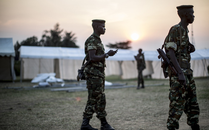 Burundian soldiers patrol during the construction of several marquees on the outskirt of Musaga neighbourhood in Bujumbura on 28 June, 2015. The marquees will be used as polling places, away from the restive district center. Picture: AFP.