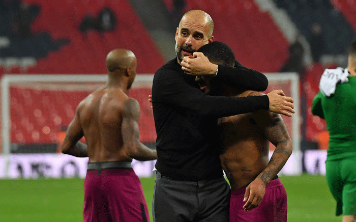 Manchester City manager Pep Guardiola embraces midfielder Raheem Sterling on the pitch after the English Premier League football match between Tottenham Hotspur and Manchester City at Wembley Stadium in London, on 14 April 2018. Picture: AFP