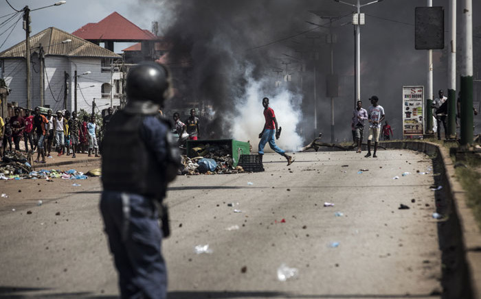 A protester walks in front of a cloud of tear gas, during a mass protest the morning after preliminary results were released for five communes in Conakry on 21 October 2020. Picture: AFP