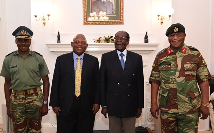 A screengrab shows Zimbabwe President Robert Mugabe (2R) as he poses alongside Zimbabwe Defence Forces Commander General Constantino Chiwenga (R) and South African envoys at State House in Harare. Picture: AFP