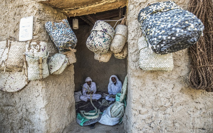 """Craftsmen work on traditional palm wicker baskets at their shop in Egypt's western desert oasis of Siwa, some 600 kilometres from the capital, on 6 November 2020. In Egypt's western desert oasis of Siwa, the """"Siwi"""" local Berber dialect remains clinging to life in the face of the dominance of Arabic which is used by only a few adults as their main language. Picture: AFP."""