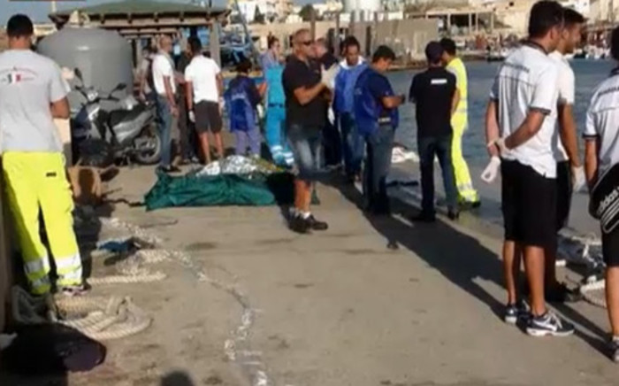 FILE: Rescuers and covered corpses of immigrants near Lampedusa early on October 3. At least 92 asylum-seekers drowned and 150 were rescued after a boat carrying some 500 people caught fire and capsized near an Italian island. Picture: AFP.