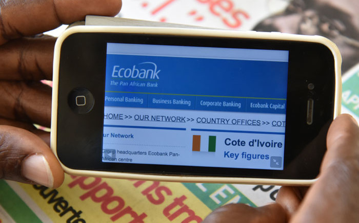 FILE: A man looks at Panafrican bank Ecobank's website to consult his account on his mobile phone on 24 April, 2015 in Abidjan. Picture: AFP