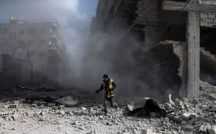FILE: A civil defence volunteer, known as the White Helmets, checks the site of a regime air strike in the rebel-held town of Saqba, in the besieged Eastern Ghouta region. Picture: AFP.