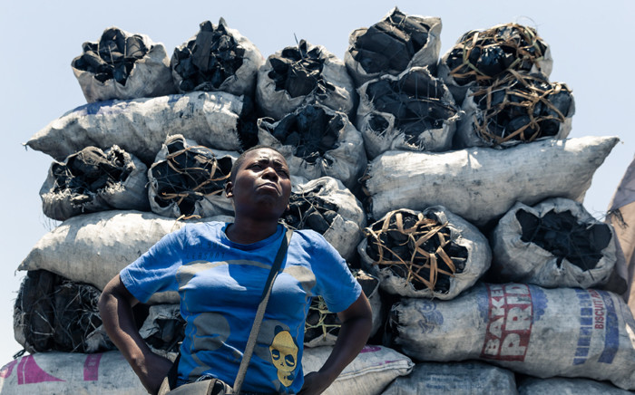 Prudence Mkonyo, a charcoal vendor in Zimbabwe, stands beside 50-kilogram polythene bags full of charcoal piled on top of each other as she sells her wares at Mbare Musika Market in Harare