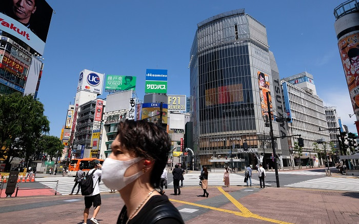 A man wearing a face mask amid concerns over the spread of the COVID-19 coronavirus crosses the Shibuya crossing in Tokyo on 17 May 2020. Picture: AFP