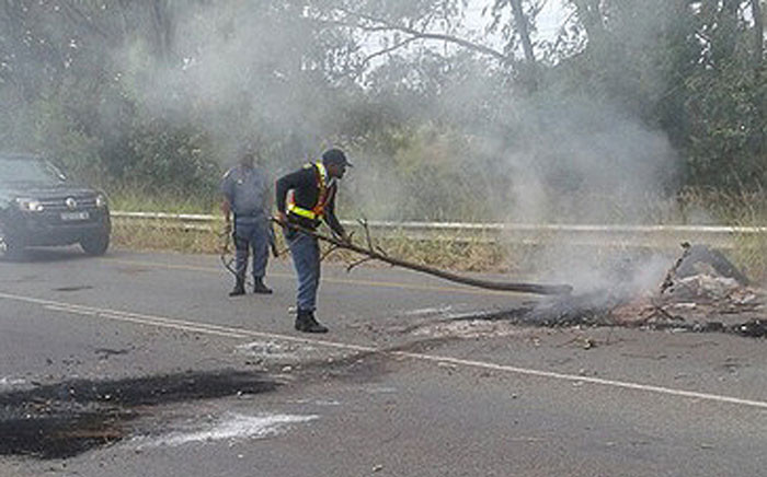 FILE: A police officer clears debris following a protest by taxi operators in Uitenhage on 10 June 2016. Pidture: @SAPoliceService via Twitter.