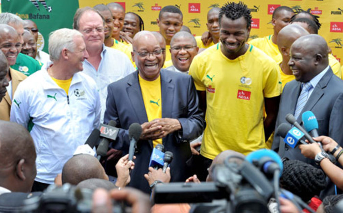 President Jacob Zuma receives a Bafana Bafana team jersey from Captain Bongani Khumalo while Coach Gordon Igesund and Deputy Minister of sports Gert Oosthuizen look on. Picture: GCIS.