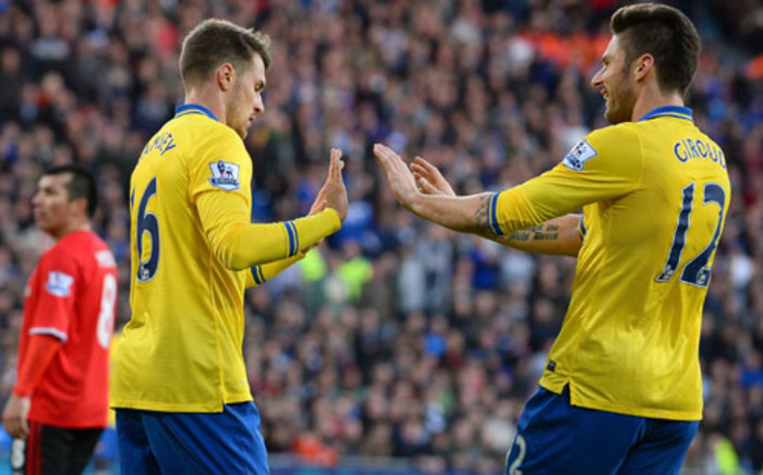 Cardiff : Arsenal's Welsh midfielder Aaron Ramsey (L) refuses to celebrate with French striker Olivier Giroud after scoring the opening goal against his former club Cardiff City during their English Premier League football match on 30 November 2013. Picture: AFP/ANDREW YATES
