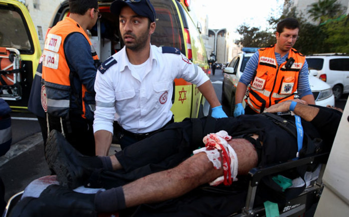 A wounded Israeli man is taken to an ambulance after his wounded leg was bandaged at the scene of an attack at a synagogue in a religious area of Jerusalem, 18 November 2014. Picture: EPA.