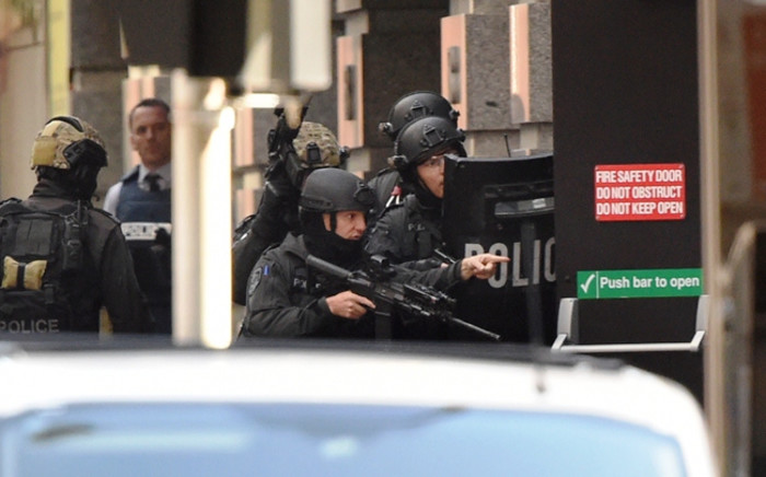Police gesture as a hostage (unseen) escapes from an emergency exit during a hostage siege in the central business district of Sydney on 15 December 2014. Picture: AFP.
