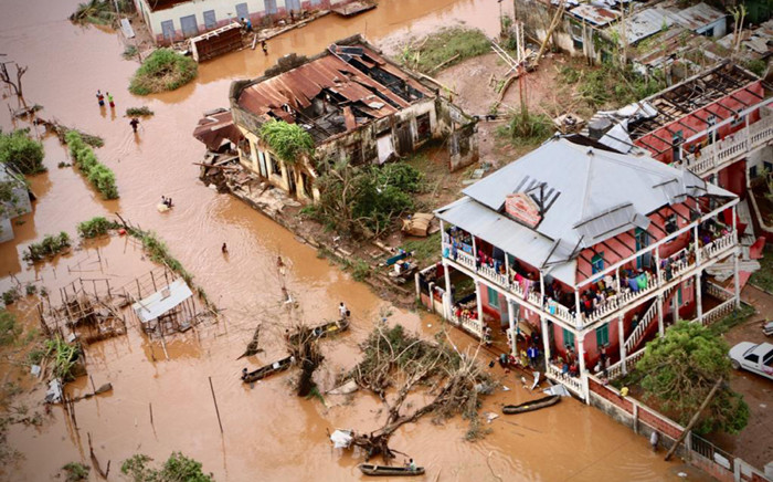 FILE: People walk on the flooded street of Buzi, central Mozambique, on 20 March 2019 after the passage of the cyclone Idai. International aid agencies raced on 20 March to rescue survivors and meet spiralling humanitarian needs in three impoverished countries battered by one of the worst storms to hit southern Africa in decades. Picture: AFP