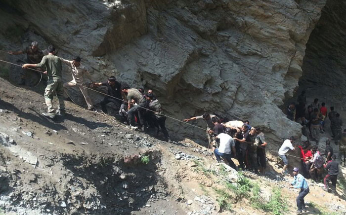 Indian police personnel and locals carry injured and dead from the site of a bus accident in Ramban district, about 140km from Jammu on July 16, 2017. Picture: AFP.