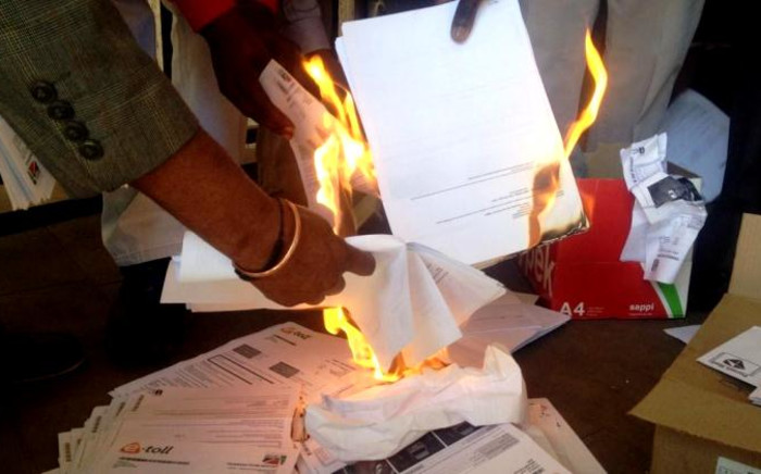 People burn their e-toll bills at an event to launch the next phase of Cosatu's defiance campaign against the collection system, Braamfontein, Johannesburg, 24 July 2014. Picture: Govan Whittles/EWN.