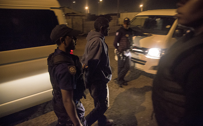 A man is moved to a police vehicle after members of Cape Town's Gang and Drug Taskforce arrested him for drug possession in Kalksteenfontein. Picture: Thomas Holder/EWN