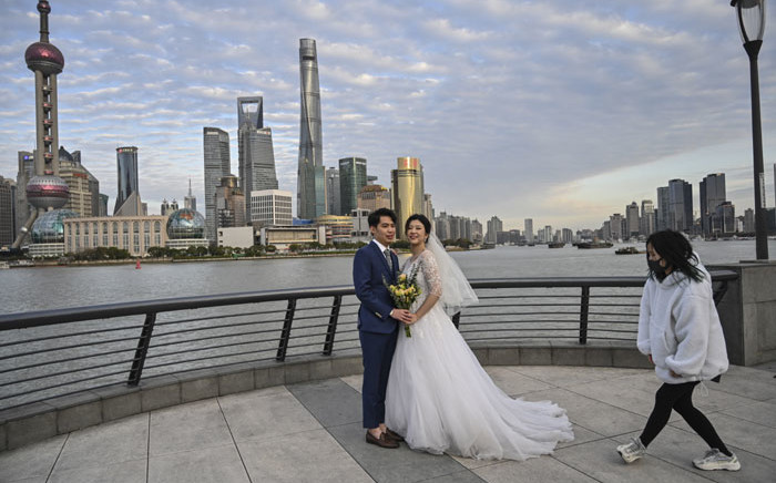 A woman wearing a facemask, amid concerns over the spread of the COVID-19 coronavirus, assists a couple during a wedding photo-shoot on the Bund promenade in Shanghai, on 16 March 2020. Picture: AFP