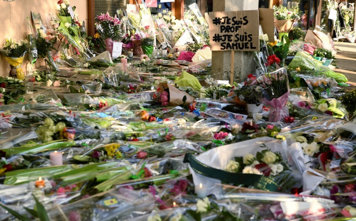 A photo shows flowers and a placard reading 'I am a teacher, I am Samuel' at the entrance of a middle school in Conflans-Sainte-Honorine, 30kms northwest of Paris, on 17 October 2020, after a teacher was decapitated by an attacker who has been shot dead by policemen. Picture: AFP.
