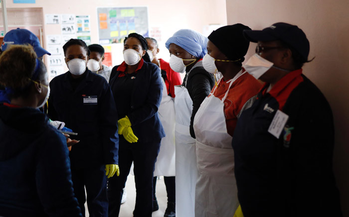 A team of cleaners having a meeting inside the Duduza Clinic that has been shut down after a nurse was found positive for the COVID-19 coronavirus in Ekurhuleni, on 2 April 2020. Picture: AFP.