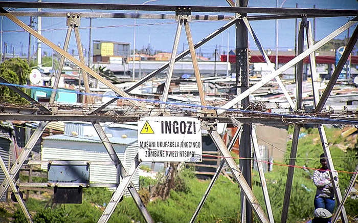 A sign warning of high electrical current hangs on a pylon in Khayelitsha, as wires from illegal connections run around it. Picture: Thomas Holder/EWN.