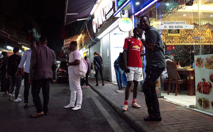 """FILE: People gather on a street in the """"Little Africa"""" district in Guangzhou, the capital of southern China's Guangdong province on 2 March 2018. Picture: AFP"""
