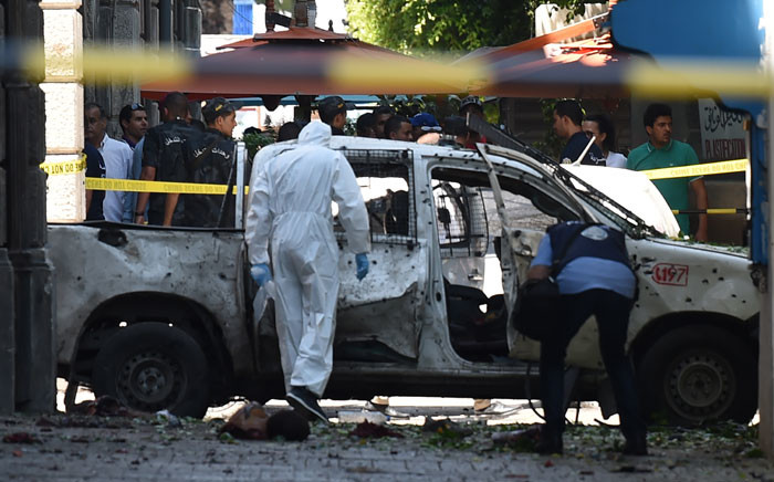 Body parts lie next to a shrapnel riddled vehicle as Tunisian forensic work at the site of attack in the Tunisian capital's main avenue Habib Bourguiba on 27 June 2019. Picture: AFP