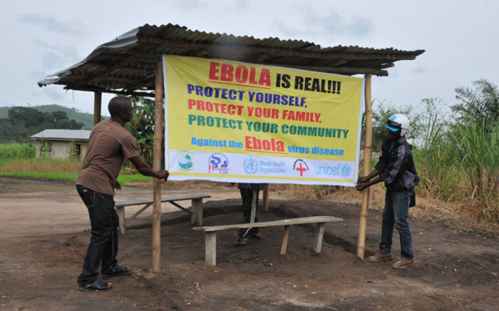 World Health Organisation volunteers putting up a banner warining people about the realness of the Ebola outbreak in West Africa. Picture: Official WHO Facebook page.
