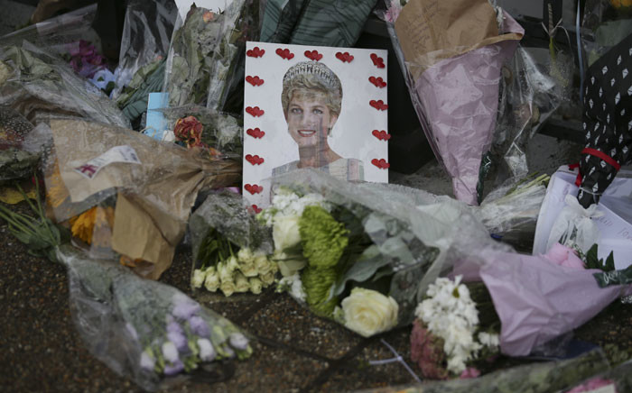 FILE: Floral tributes and photographs are seen outside one of the entrances of Kensington Palace to mark the coming 20th anniversary of the death of Diana, Princess of Wales, in London on 30 August 2017. Britain's Diana, Princess of Wales, died in a high-speed car crash in Paris on 31 August 1997. Picture: AFP