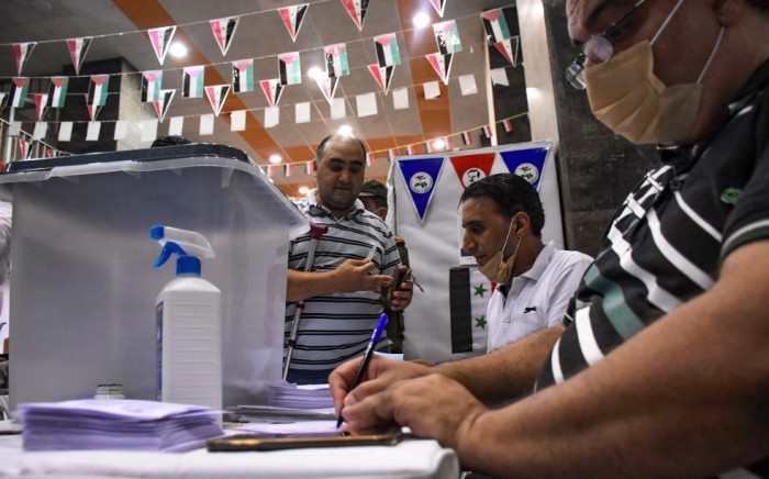 A man registers to vote at a voting station in the northern Syrian city of Aleppo on 19 July 2020, during the parliamentary elections. Syrians vote today to elect a new parliament as the Damascus government grapples with international sanctions and a crumbling economy after retaking large parts of the war-torn country. Picture: AFP