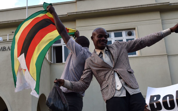 FILE: People wave national flags as they celebrate outside the parliament in Harare, after the resignation of Zimbabwe's president Robert Mugabe on November 21, 2017. Picture: AFP