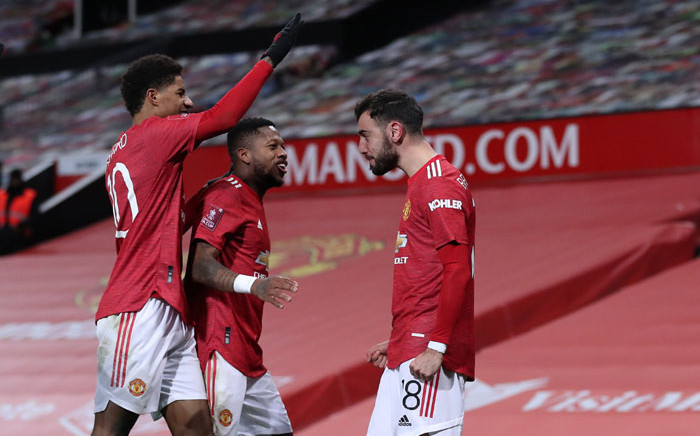 Manchester United midfielder Bruno Fernandes (R) celebrates scoring his team's third goal during the English FA Cup fourth round football match between Manchester United and Liverpool at Old Trafford in Manchester, north west England, on 24 January 2021. Picture: Martin Rickett/AFP