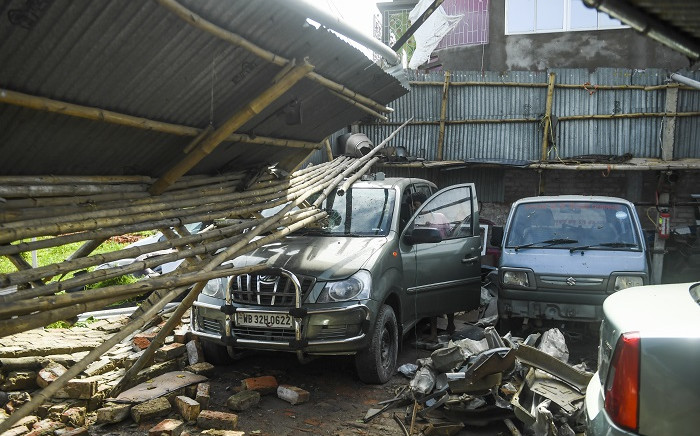 A man checks cars in a garage damaged by cyclone Amphan in Satkhira on 21 May 2020.  Picture: AFP