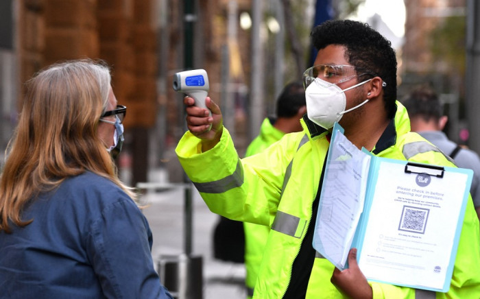 A health official checks the temperature of a resident at a COVID-19 vaccination centre in Sydney on 27 July 2021. Picture: AFP