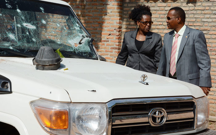 Burundian investigators stand next to the shrapnel-riddled vehicle in which Tutsi General and security advisor to Burundi's vice president Athanase Kararuza was killed on 25 April 2016 in Bujumbura. Picture: Onesphore Nibigira/AFP.