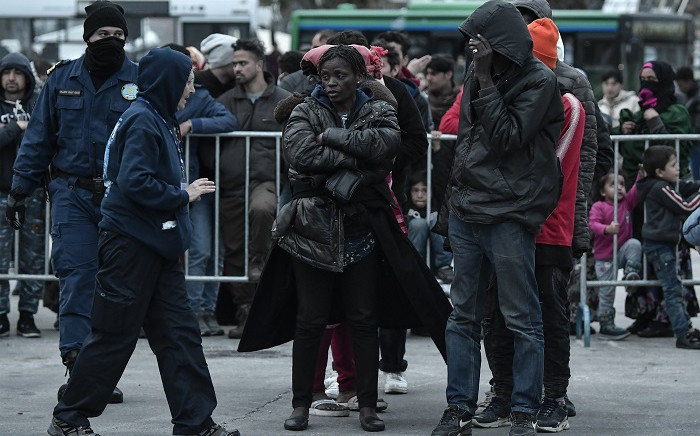 First groups of recently arrived refugees and migrants gather before getting on board a warship provided for their accommodation on the port of Mytilene on the island of Lesbos, on 4 March 2020. Picture: AFP