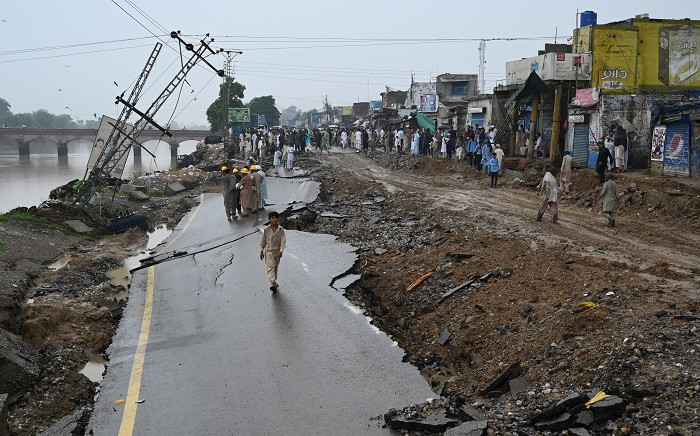 People gather next to a damaged road in an earthquake-hit area on the outskirts of Mirpur on 25 September 2019. Picture: AFP