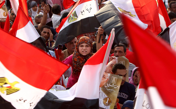 Hundreds of supporter of presidential candidate Ahmed Shafiq, the last prime minister of ousted leader Hosni Mubarak, hold up the national flag as they demonstrate in Nasr city on the outskirts of Cairo, on June 23, 2012. Tensions soared in Egypt a day before the result of a divisive presidential election and as the Muslim Brotherhood sparred with the ruling generals over what it sees as a military power grab. Picture: AFP
