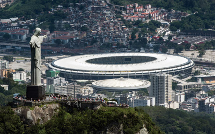 Aerial view of the Christ the Redeemer statue atop Corcovado Hill and the Mario Filho (Maracana) stadium in Rio de Janeiro, Brazil, on 3 December, 2013. Picture: AFP.