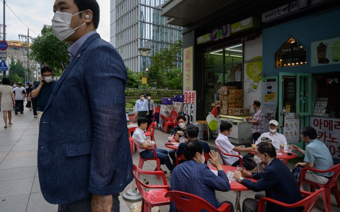FILE: Pedestrians wearing face masks as a preventative measure against the COVID-19 coronavirus sit on a street in Seoul on 31 August 2020. South Korea decided on 28 August to tighten coronavirus curbs further in the greater Seoul area as it seeks to contain growing clusters in the region. Picture: AFP.