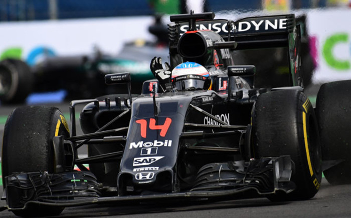 McLaren F1 driver Fernando Alonso waves from his car at the end of a race. Picture: AFP